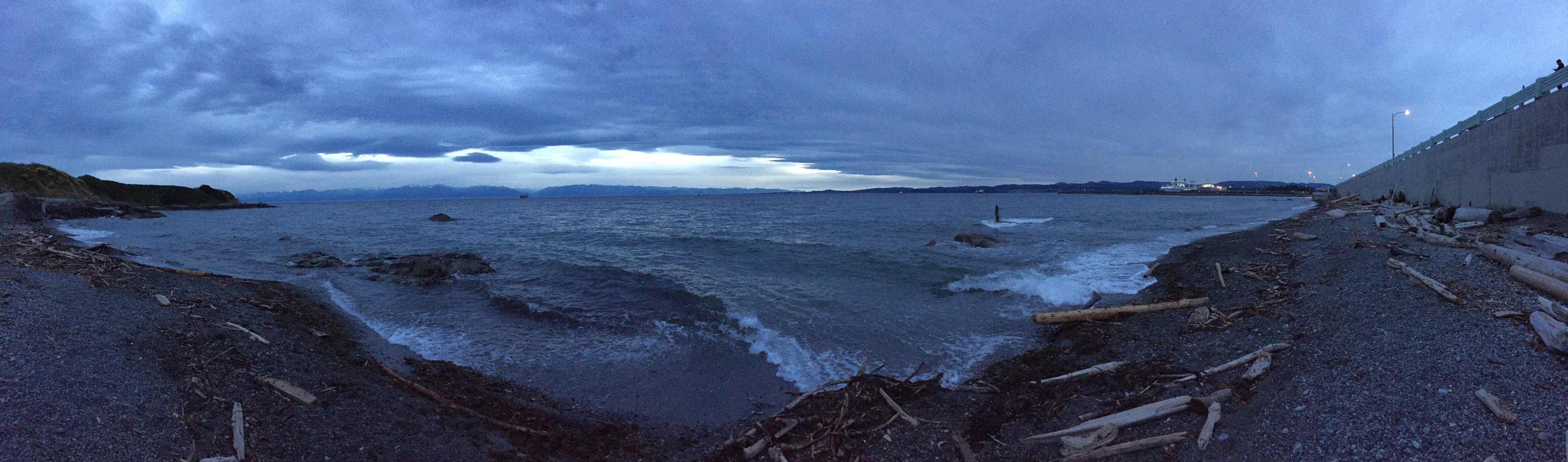 panoramic shot of a rocky shoreline with dark blue tones throughout