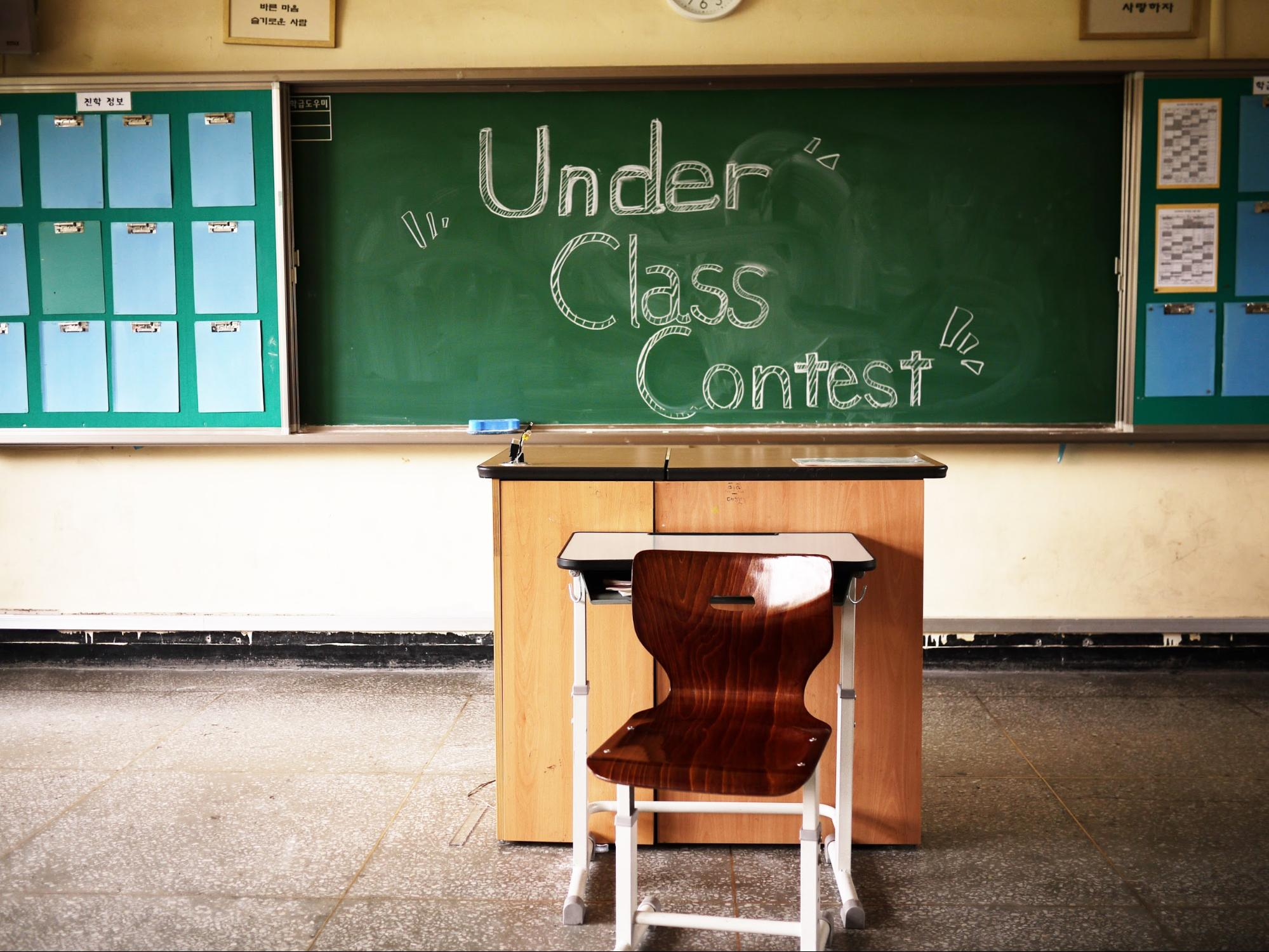 """An image of the front of a classroom. There is an empty chair and podium and the words """"Under Class Contest"""" are written on the chalkboard."""