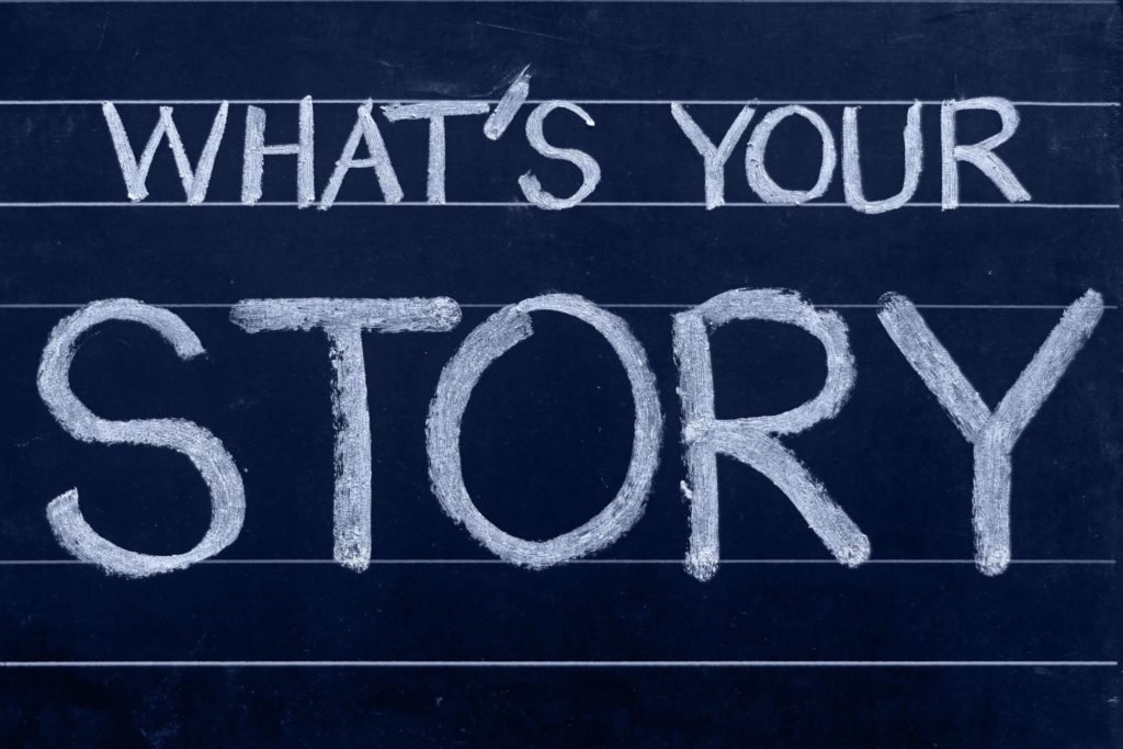 """The words """"what's your story"""" are written on a chalkboard. The word """"story"""" is written in a much larger size."""