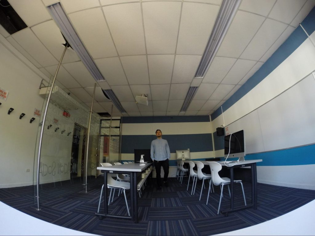 A fish-eye lens emphasizes the space around a man who is standing in a classroom.