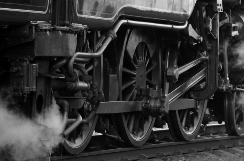 Image focusing on the wheels of a train with steam rising from the undercarriage. The shift of the academic institution to an increasingly capitalistic system is like a run-away train, powerful and yet rushing headlong to its own destruction.